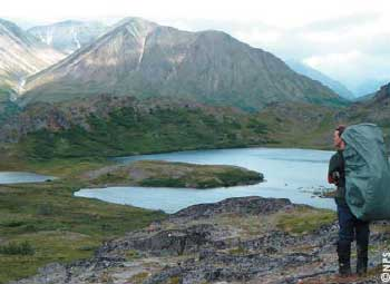 A hiker enjoys the views of Lake Clark