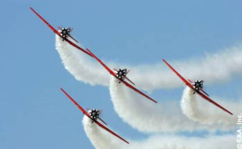 The AeroShell Aerobatic Team performs one of its signature maneuvers during the afternoon air show at EAA AirVenture.